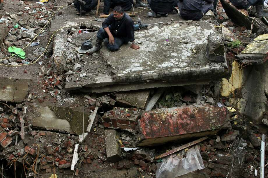 A rescue worker rests at the site of a collapsed building in Mumbai, India, Saturday, Sept. 28, 2013. Frantic relatives kept up a vigil at the site of the collapsed apartment building as the search for survivors grew bleak on Saturday. Photo: AP