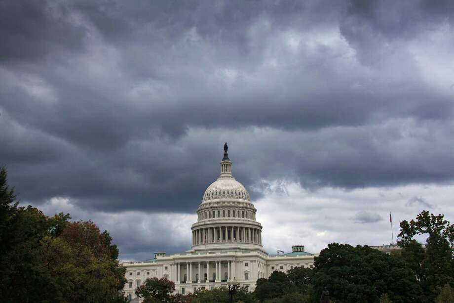 Dark clouds hang over the U.S. Capitol in Washington on Saturday, Sept. 28, 2013. A midnight Monday deadline is approaching for Congress to break an impasse over funding the government. In a rare weekend session, lawmakers from both parties urged one another to give ground in their fight over preventing a federal shutdown. Photo: AP