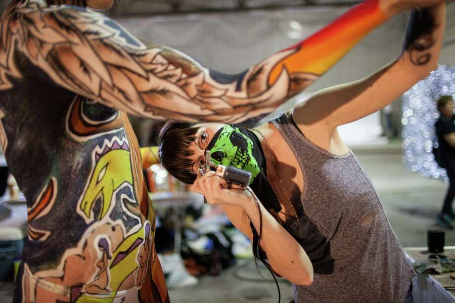 Texas artist Elizabeth Schieffer paints on model Lon Lawson during the Living Art America - Bodies as a Work of Art body painting competition Saturday, Sept. 28, 2013 in Atlanta, GA. Forty artist from nine countries are competing in the first sanctioned World Bodypainting Association event held in the United States. Photo: AP