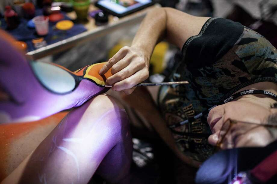 Wyoming artist Dawn DeWitt paints on model Brittaney Isphording during the Living Art America - Bodies as a Work of Art body painting competition Saturday, Sept. 28, 2013 in Atlanta, GA. Forty artist from nine countries are competing in the first sanctioned World Bodypainting Association event held in the United States. Photo: AP