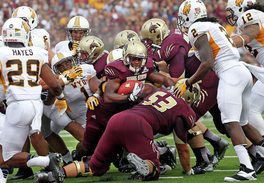 Bobcat running back Robert Lowe battles in the line for yards in the first quarter as Texas State hosts Wyoming at Bobcat Stadium in San Marcos on September 28, 2013