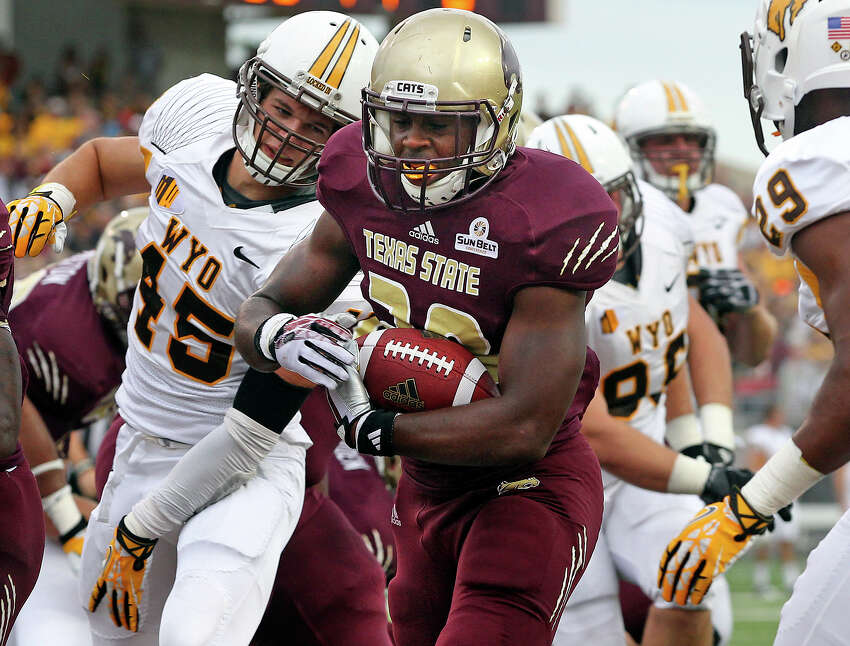Bobcat running back Robert Lowe slips into the end zone in the first quarter past Lucas Wacha as Texas State hosts Wyoming at Bobcat Stadium in San Marcos on September 28, 2013