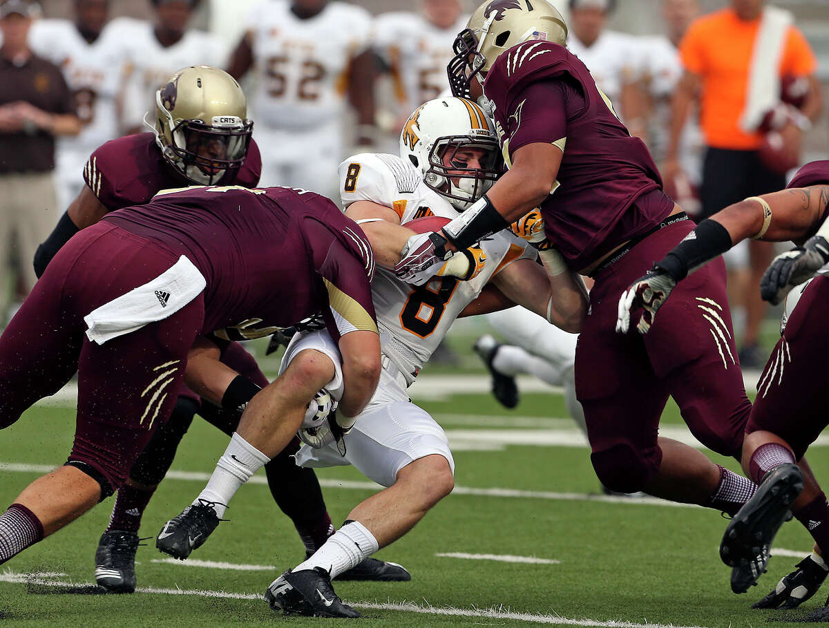 Cowboy running back Brandon Miller is stopped for a loss by Bobcat defenders Blake McColloch (left) and Jordan Norfleet as Texas State hosts Wyoming at Bobcat Stadium in San Marcos on September 28, 2013