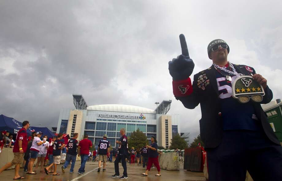 Texans fan Kevin DeVil, or General DeVil, holds up a foam finger for a fan to take a picture before the game. Photo: Cody Duty, Houston Chronicle