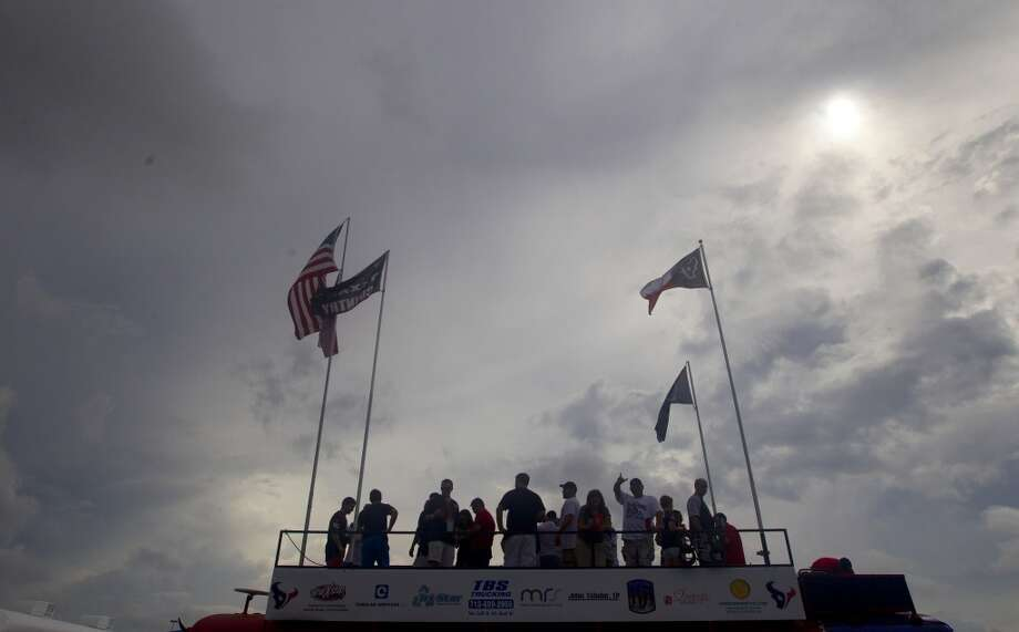 Texans fans stand atop a party bus while tailgating. Photo: Cody Duty, Houston Chronicle