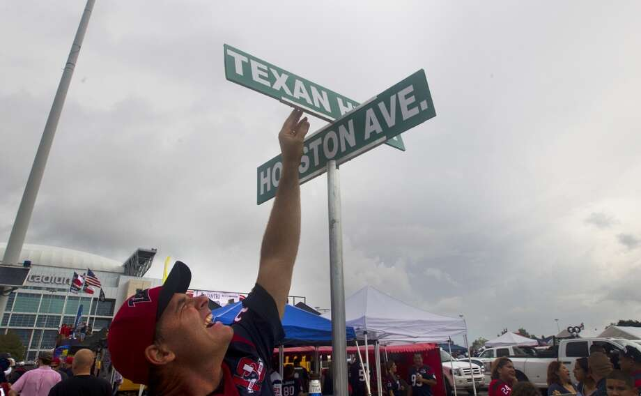 Texans fan Brett Galliford adjusts two street signs marking an intersection at Texan Hwy. and Houston Ave. Photo: Cody Duty, Houston Chronicle