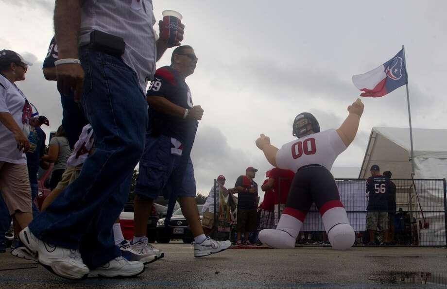 Texans fans walk by an inflatable Texan football player. Photo: Cody Duty, Houston Chronicle