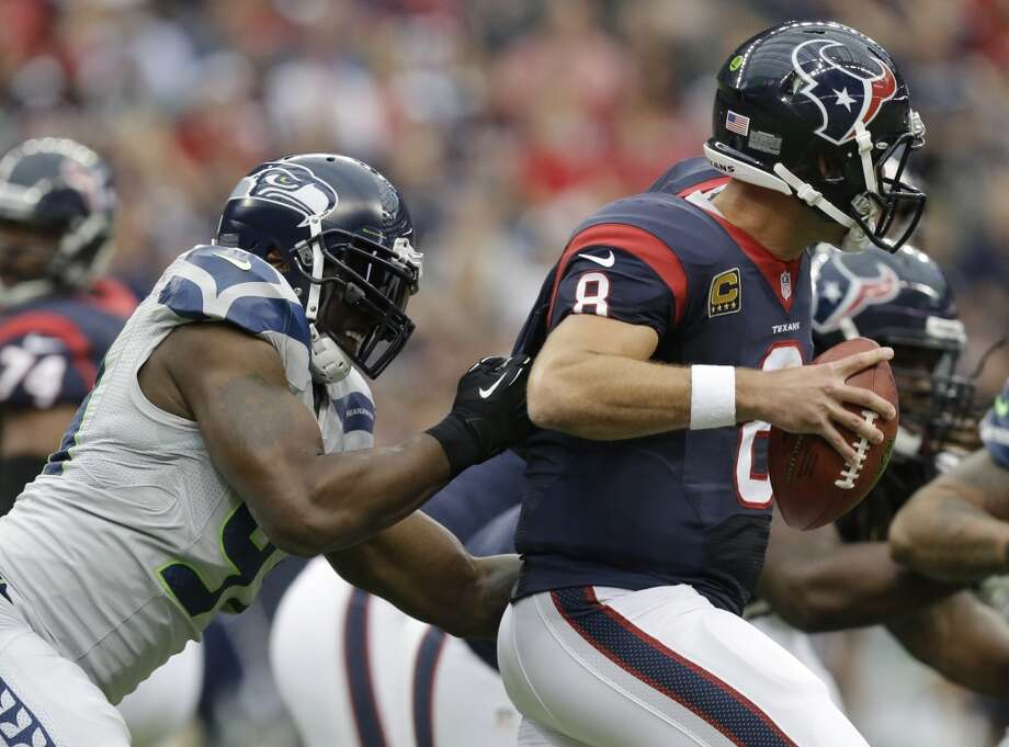 Seattle Seahawks' Chris Clemons, left, grabs Houston Texans' Matt Schaub (8) who looks to pass during the first quarter an NFL football game on Sunday, Sept. 29, 2013, in Houston. Photo: Patric Schneider, Associated Press