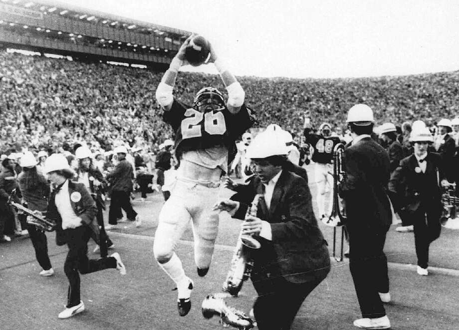 "Cal's Kevin Moen leaps after scoring the winning touchdown in ""The Play"" with the Stanford band on the UC Berkeley field on Nov. 18, 1982. Moen weaved his way through dozens of players and band members to score as time expired to give Cal a 25-20 win over Stanford. Photo: Robert Stinnett, AP"