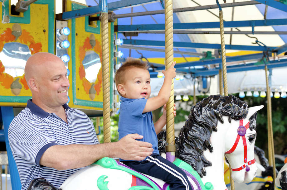 Tom Gallagher, of Stamford, smiles as his son, Alec, 1.5, rides a carousel horse during the final day of the Greek Fest held at Archangels Greek Orthodox Church on Bedford Street in Stamford on Sunday, Sept. 29, 2013. Photo: Amy Mortensen