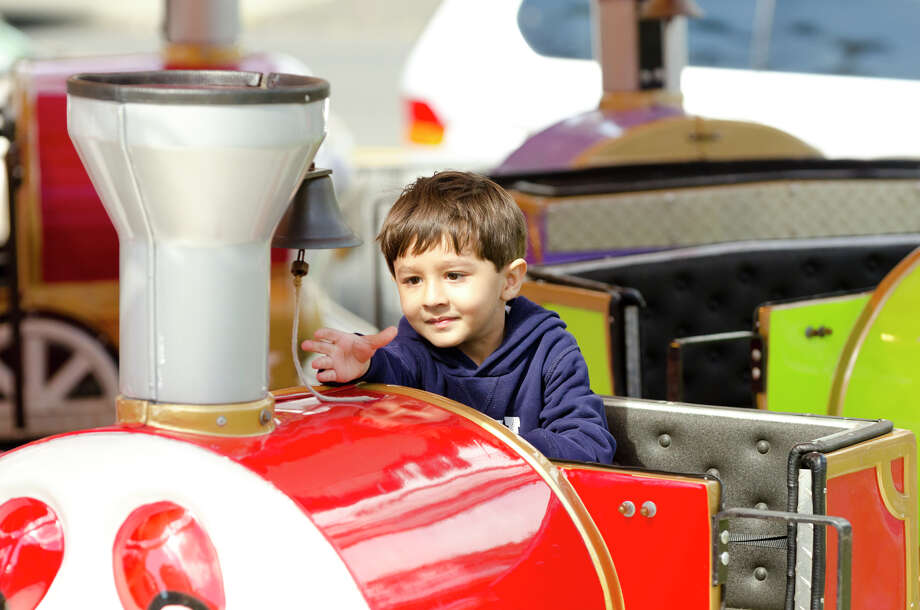 "Parv Shah, 3, of Stamford, reaches out to ring the bell of the ""Jolly Choo-Choo"" train during the final day of the Greek Fest held at Archangels Greek Orthodox Church on Bedford Street in Stamford on Sunday, Sept. 29, 2013. Photo: Amy Mortensen"