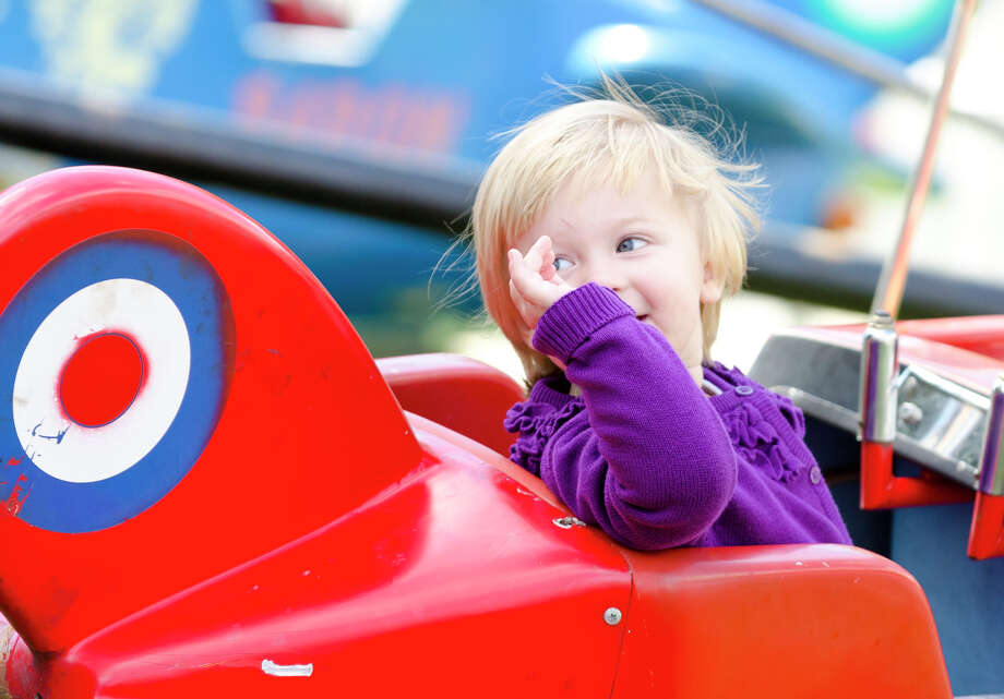 "Charlotte Dianis, 2, of Stamford, waves to her father, Chuck, as she rides the ""Red Baron"" plane ride during the final day of the Greek Fest held at Archangels Greek Orthodox Church on Bedford Street in Stamford on Sunday, Sept. 29, 2013. Photo: Amy Mortensen"