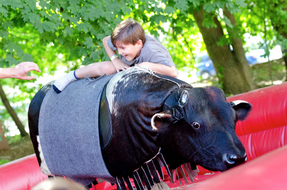 Demetre Zoumboulis, 7, of Stamford, hangs on with all his might as he rides the mechanical bull during the final day of the Greek Fest held at Archangels Greek Orthodox Church on Bedford Street in Stamford on Sunday, Sept. 29, 2013. Photo: Amy Mortensen