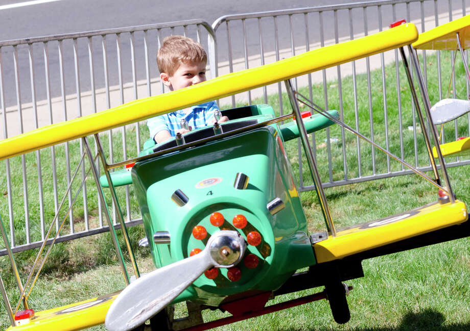 Matthew Aiello, 3, of Stamford, looks out over the top of his biplane during the final day of the Greek Fest held at Archangels Greek Orthodox Church on Bedford Street in Stamford on Sunday, Sept. 29, 2013. Photo: Amy Mortensen