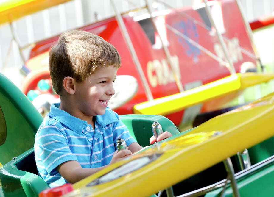Matthew Aiello, 3, of Stamford, grabs the controls of his biplane as he pretends to fly around the festival grounds during the final day of the Greek Fest held at Archangels Greek Orthodox Church on Bedford Street in Stamford on Sunday, Sept. 29, 2013. Photo: Amy Mortensen