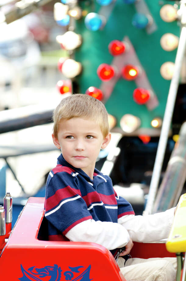 """Ethan Dianis, 6, of Stamford, takes a spin on the """"Red Baron"""" plane ride during the final day of the Greek Fest held at Archangels Greek Orthodox Church on Bedford Street in Stamford on Sunday, Sept. 29, 2013. Photo: Amy Mortensen"""