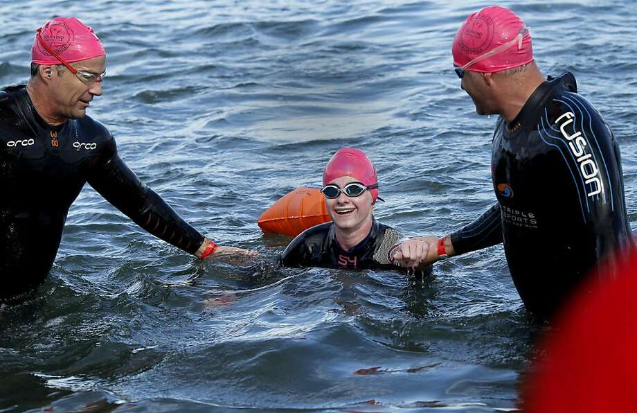 Jim Stelzer (left) and Tom Palmer (right) accompany Katie Cuppy out of San Francisco Bay after their successful swim from Alcatraz to Aquatic Park. Photo: Brant Ward, The Chronicle