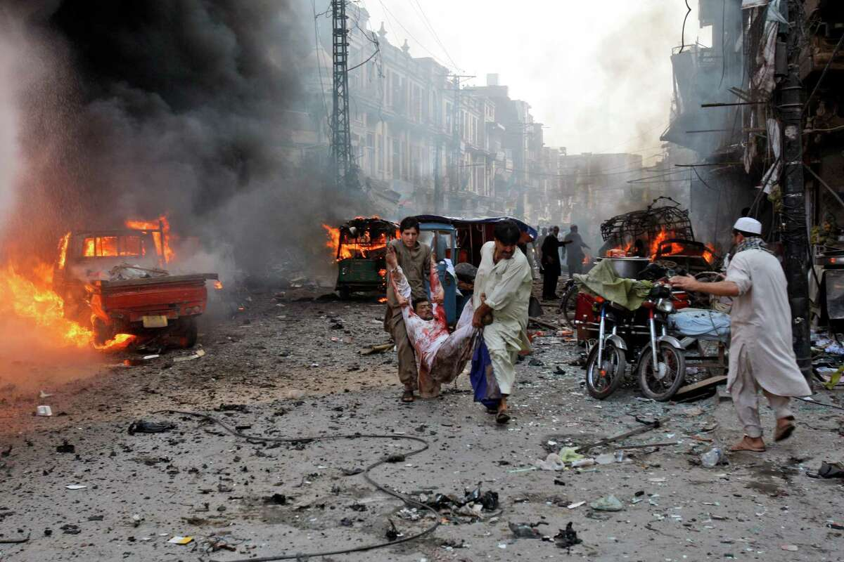 Pakistani men carry an injured man away from the site moments after a car bomb attack in Peshawar, Pakistan, Sunday, Sept. 29, 2013. A deadly car bomb exploded on a crowded street in northwestern Pakistan Sunday, in the third blast to hit the troubled city of Peshawar in a week, officials said.