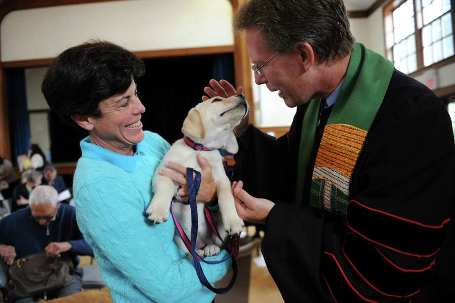 Kate McNamara, of Greenwich, held a Labrador retriever Soleil, 3-months-old, while the Rev. Dr. Edward G. Horstmann blesses Soleil at Round Hill Community annual Blessing of the Animals, in Greenwich, Conn., Sunday, Sept. 29, 2013. Photo: Helen Neafsey / Greenwich Time