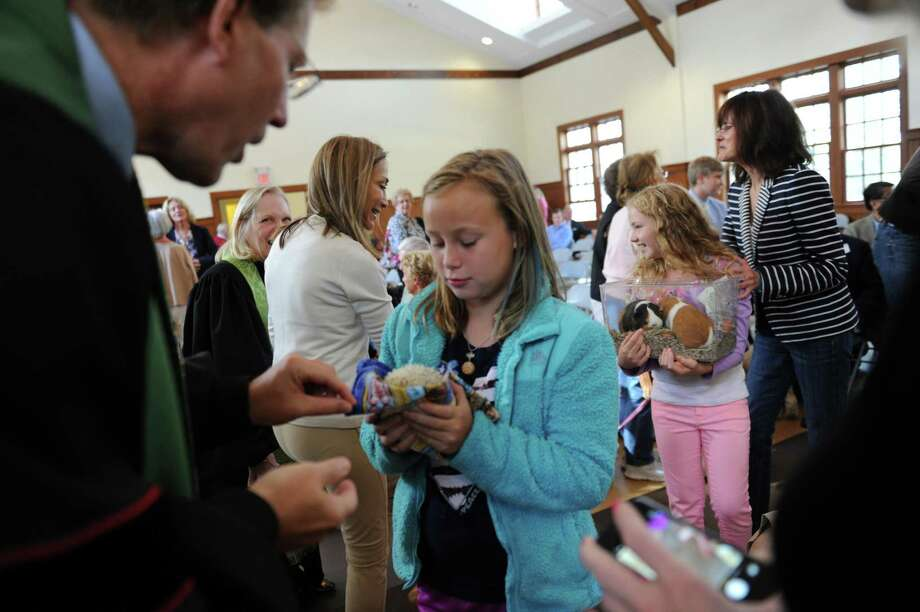 The Rev. Dr. Edward G. Horstmann blesses a hedgehog of Celeste Walstrom-Vangor at Round Hill Community annual Blessing of the Animals, in Greenwich, Conn., Sunday, Sept. 29, 2013. Photo: Helen Neafsey / Greenwich Time