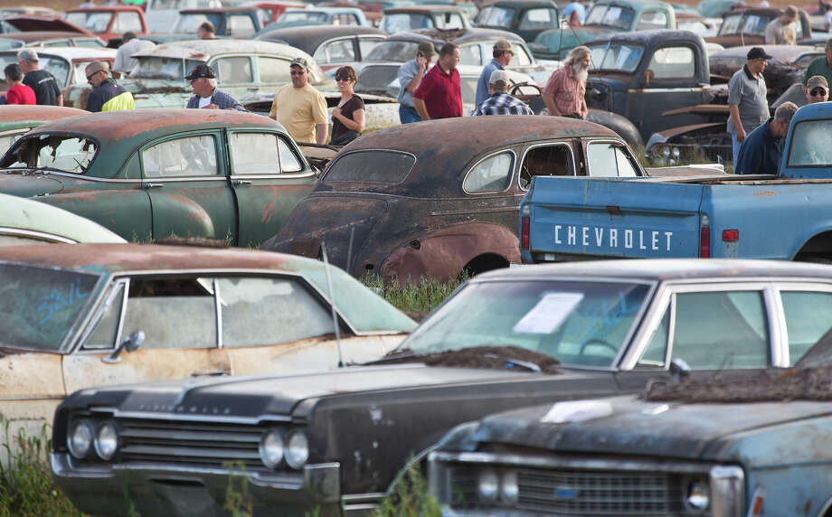 Potential bidders browse through some of about 500 vintage cars and trucks during a preview for an auction of  former Lambrecht Chevrolet dealership vehicles in Pierce, Neb., Friday Sept. 27, 2013. The auction begins Saturday. (AP Photo/The Omaha World-Herald/Ryan Soderlin) MAGS OUT; ALL NEBRASKA LOCAL BROADCAST, TV OUT Photo: AP