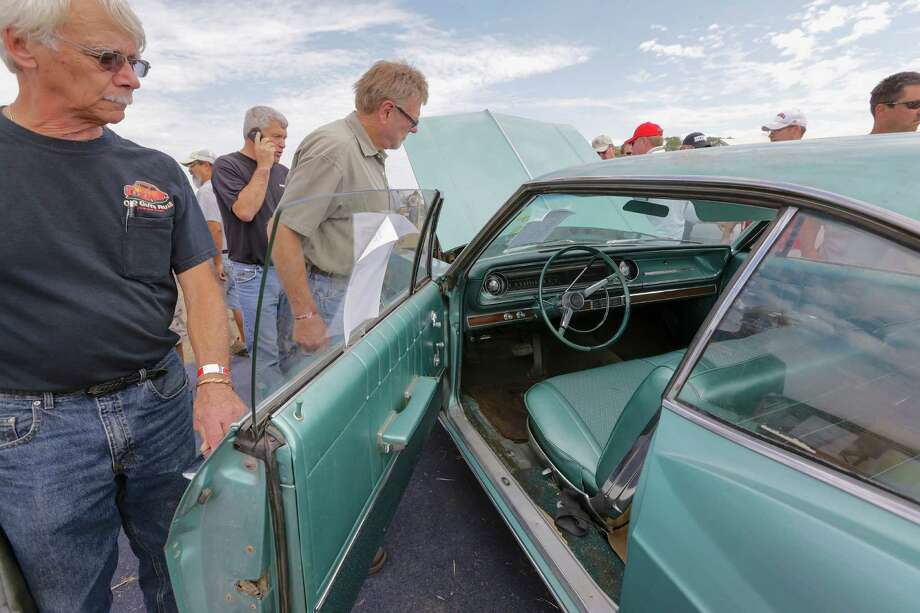 Car buffs look over 1965 Chevrolet Impala 2 door hardtop during a preview for an auction of vintage cars and trucks from the former Lambrecht Chevrolet dealership in Pierce, Neb., Friday Sept. 27, 2013. The auction takes place on Saturday and Sunday. Photo: AP