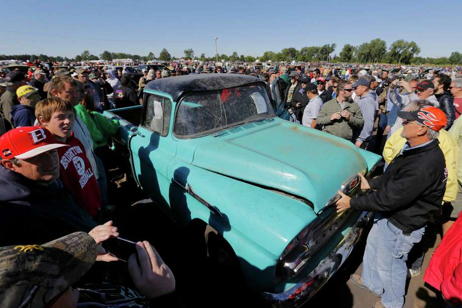 Crowds mill around a rare sky-blue, 1958 Chevy Cameo pickup driven 1.3 miles which sold at the Lambrecht Chevrolet auction in Pierce Neb., for $140,000. A collection of barely driven vintage Chevrolets fetched more than half a million dollars on Saturday, Sept. 28, 2013, at an auction that drew car buffs from around the world to the small northeast Nebraska town. Photo: AP