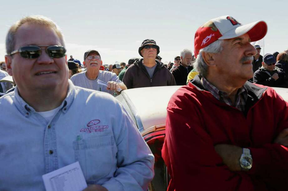 Car buffs follow the sale of a collection of barely driven vintage Chevrolets, Saturday, Sept. 28, 2013, at an auction that drew car buffs from around the world. Bidders and gawkers crowded shoulder-to-shoulder for the auction in a muddy field just west of Pierce, Neb., a town of 1,800. Photo: AP