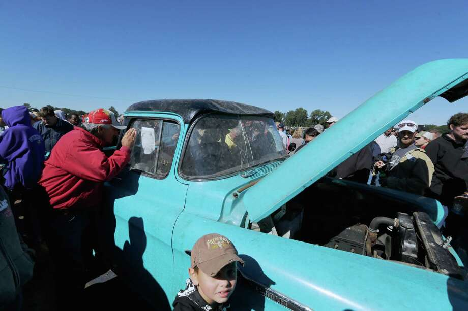 Car buffs admire a brand new 1958 Chevrolet Cameo Pickup truck that has 1.3 miles on the clock after it was sold for $140,000, Saturday, Sept. 28, 2013, at an auction that drew car buffs from around the world. Bidders and gawkers crowded shoulder-to-shoulder for the auction in a muddy field just west of Pierce, Neb., a town of 1,800. Photo: AP