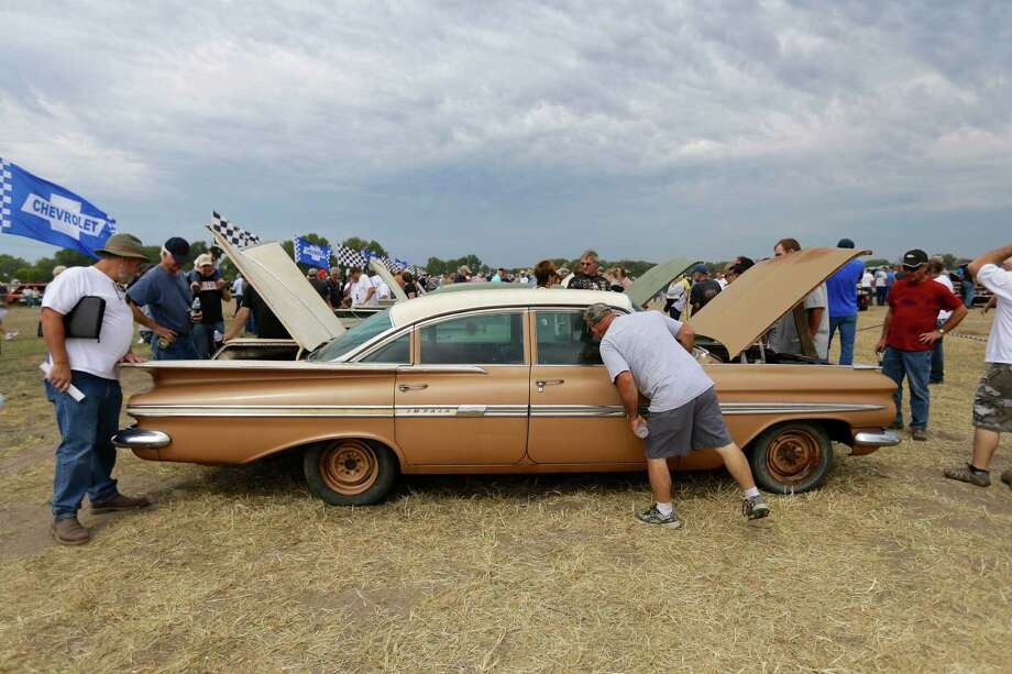 Car buffs examine a 1959 Chevrolet Impala during a preview for an auction of vintage cars and trucks from the former Lambrecht Chevrolet dealership in Pierce, Neb., Friday Sept. 27, 2013. Photo: AP