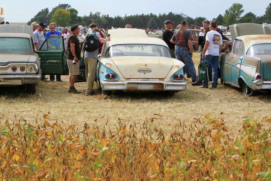 Visitors check out cars next to a soy bean field during a preview for an auction of vintage cars and trucks from the former Lambrecht Chevrolet dealership in Pierce, Neb., Friday Sept. 27, 2013. Photo: AP