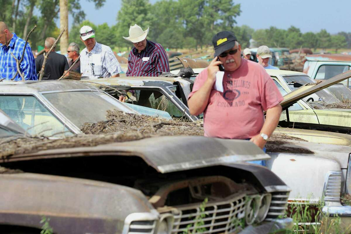 Rows of cars are examined during a preview for an auction of vintage cars and trucks from the former Lambrecht Chevrolet dealership in Pierce, Neb., Friday Sept. 27, 2013.