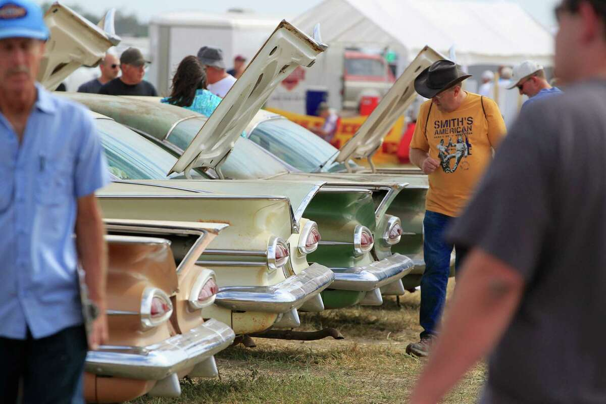 Potential buyers look over a row of Chevrolet cars during a preview for an auction of vintage cars and trucks from the former Lambrecht Chevrolet dealership in Pierce, Neb., Friday Sept. 27, 2013.