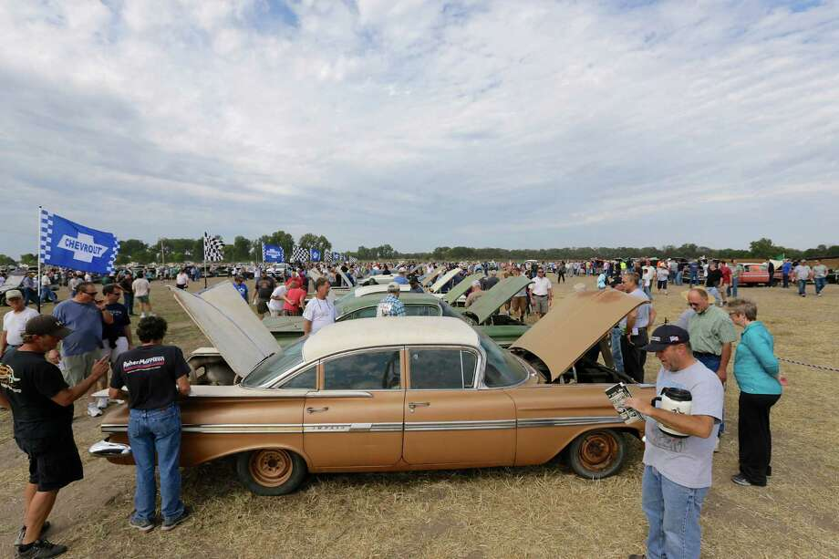 Car buffs survey a 1959 Chevrolet Impala, foreground, and other Chevrolet vehicles during a preview for an auction of vintage cars and trucks from the former Lambrecht Chevrolet dealership in Pierce, Neb., Friday Sept. 27, 2013. The auction takes place on Saturday and Sunday. Photo: AP