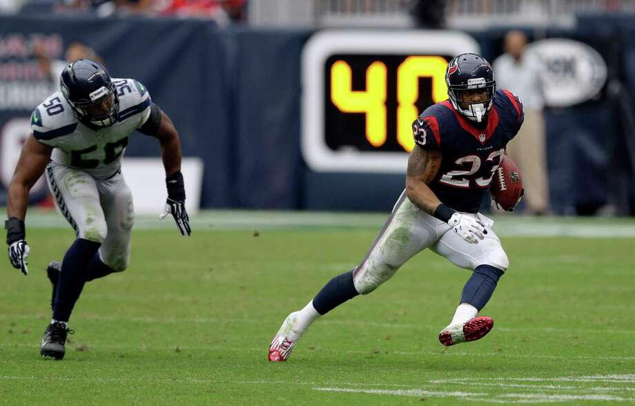 Houston Texans running back Arian Foster (23) rushes for a gain as Seattle Seahawks outside linebacker K.J. Wright (50) defends during the third quarter an NFL football game Sunday, Sept. 29, 2013, in Houston. (AP Photo/David J. Phillip) Photo: David J. Phillip, Associated Press / AP