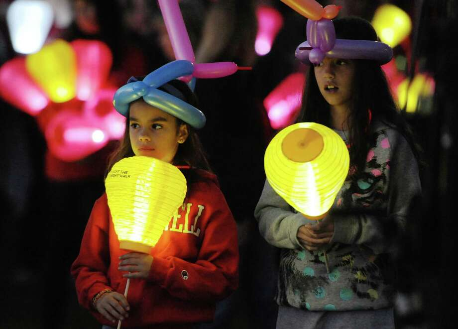 Danielle Vigneau, left, 9, and Eliza Estes, 10, of Newtown, hold gold balloons for loved ones lost at the Light the Night Walk cancer fundraiser at Newtown Youth Academy in Newtown, Conn. on Saturday, Sept. 2, 2013.  Over 400 people walked the two-mile route around the Fairfield Hills campus, carrying illuminated ballons - red for supporters, white for survivors and gold for those who lost loved ones to cancer. Photo: Tyler Sizemore / The News-Times