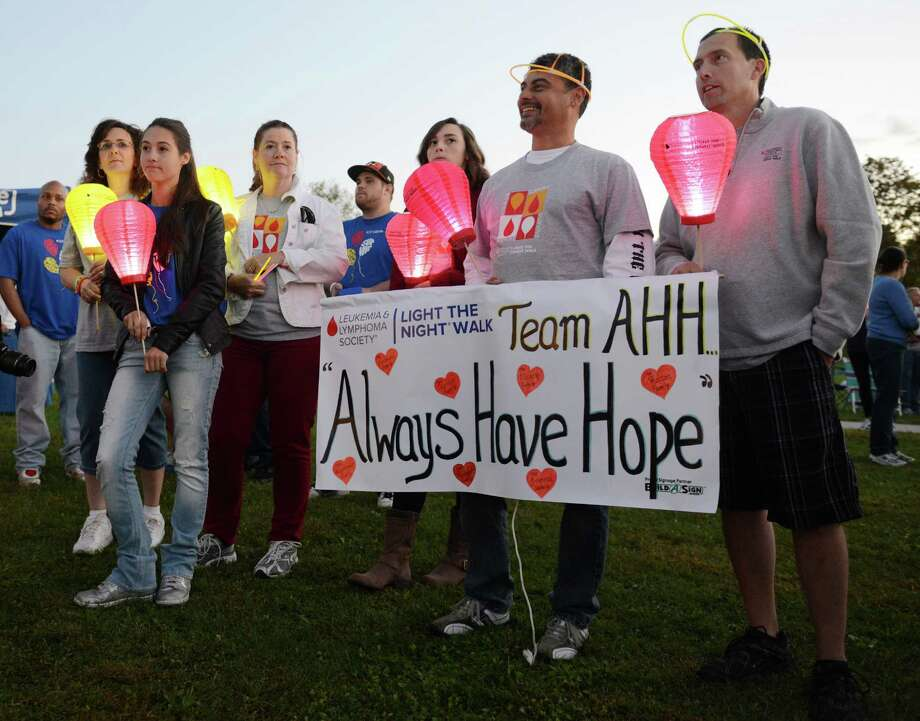 """Jim Pearson, right, and Raul Oliveira, second from right, of Sandy Hook, hold up a sign for """"Team Always Have Hope"""" at the Light the Night Walk cancer fundraiser at Newtown Youth Academy in Newtown, Conn. on Saturday, Sept. 2, 2013.  Over 400 people walked the two-mile route around the Fairfield Hills campus, carrying illuminated ballons - red for supporters, white for survivors and gold for those who lost loved ones to cancer. Photo: Tyler Sizemore / The News-Times"""