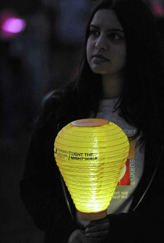 Amber Vohra, of New Fairfield, holds a gold balloon for a loved one lost at the Light the Night Walk cancer fundraiser at Newtown Youth Academy in Newtown, Conn. on Saturday, Sept. 2, 2013.  Over 400 people walked the two-mile route around the Fairfield Hills campus, carrying illuminated ballons - red for supporters, white for survivors and gold for those who lost loved ones to cancer. Photo: Tyler Sizemore / The News-Times