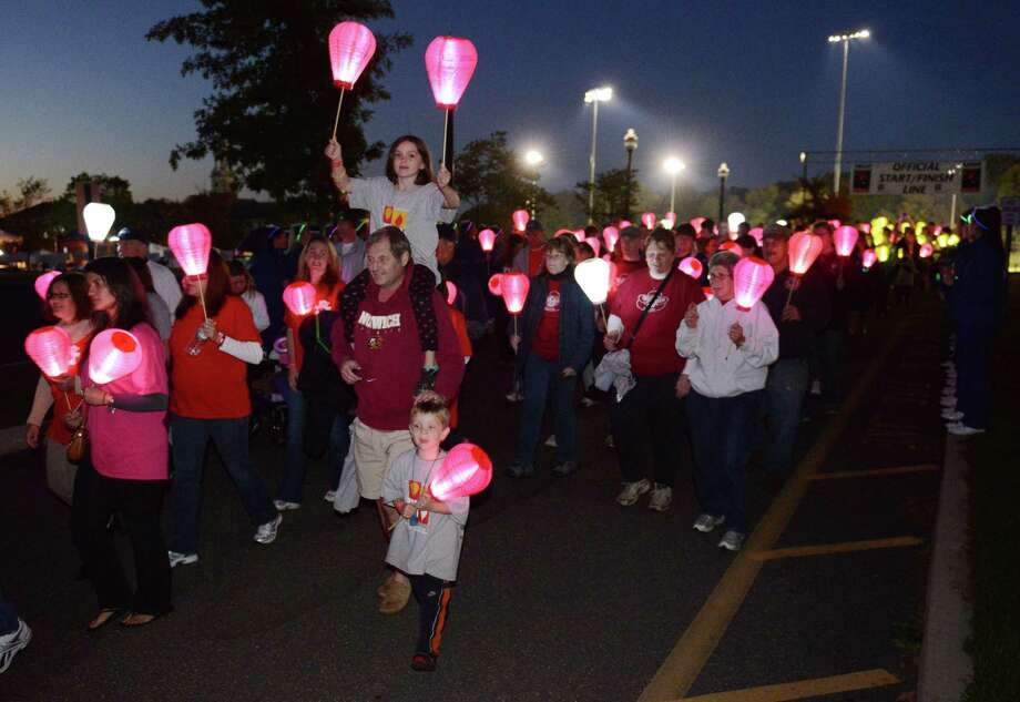 Walkers leave the starting line of the Light the Night Walk cancer fundraiser at Newtown Youth Academy in Newtown, Conn. on Saturday, Sept. 2, 2013.  Over 400 people walked the two-mile route around the Fairfield Hills campus, carrying illuminated ballons - red for supporters, white for survivors and gold for those who lost loved ones to cancer. Photo: Tyler Sizemore / The News-Times