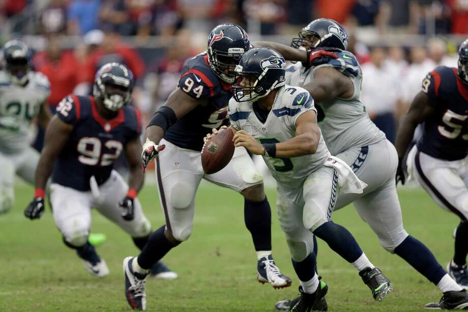 Seattle Seahawks quarterback Russell Wilson (3) scrambles away from Houston Texans defensive end Antonio Smith (94) during overtime of an NFL football game Sunday, Sept. 29, 2013, in Houston. Seattle won 23-20. (AP Photo/David J. Phillip) Photo: David J. Phillip, Associated Press / AP