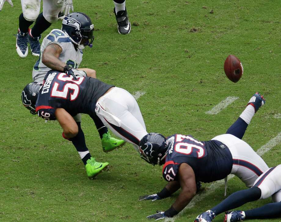 Seattle Seahawks' Marshawn Lynch, left, fumbles the ball as he is hit by Houston Texans' Brian Cushing (56) during the second quarter an NFL football game on Sunday, Sept. 29, 2013, in Houston. Houston recovered the ball. (AP Photo/David J. Phillip) Photo: David J. Phillip, Associated Press / AP