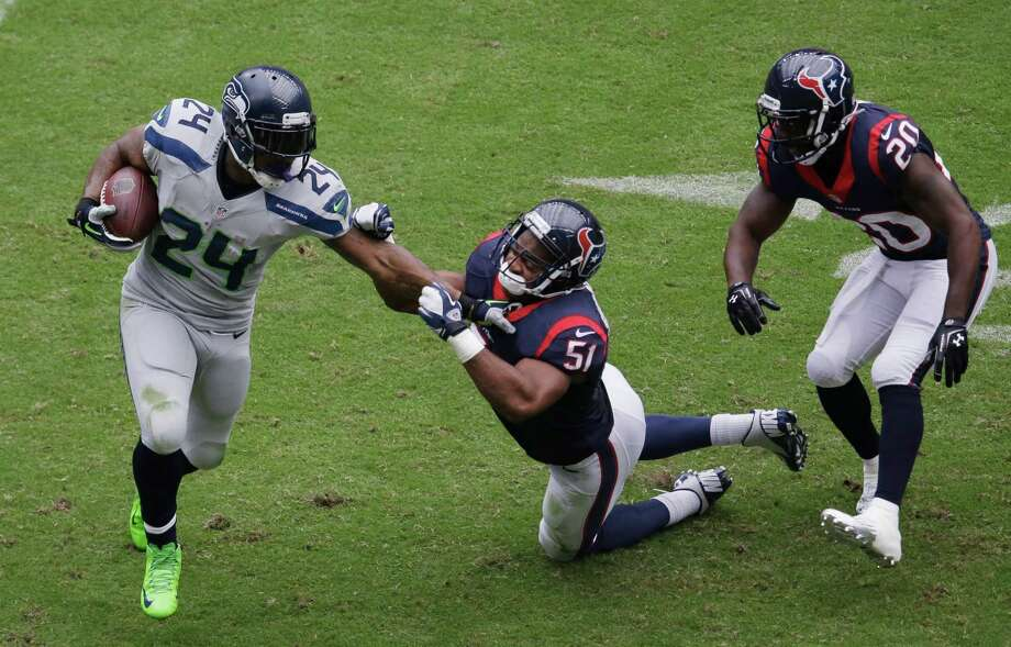 Seattle Seahawks' Marshawn Lynch (24) is pulled down by Houston Texans' Darryl Sharpton (51) during the second quarter an NFL football game on Sunday, Sept. 29, 2013, in Houston. (AP Photo/David J. Phillip) Photo: David J. Phillip, Associated Press / AP