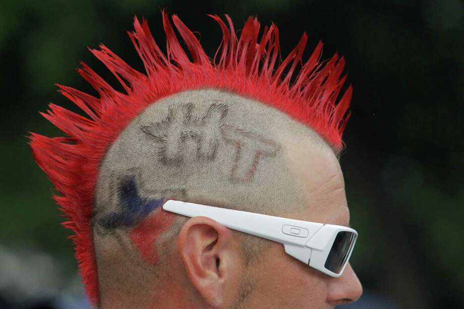 A Houston Texans fans sports colorful hair and a logo before an NFL football game against the Seattle Seahawks, Sunday, Sept. 29, 2013, in Houston. (AP Photo/Patric Schneider) Photo: Patric Schneider, Associated Press / FR170473