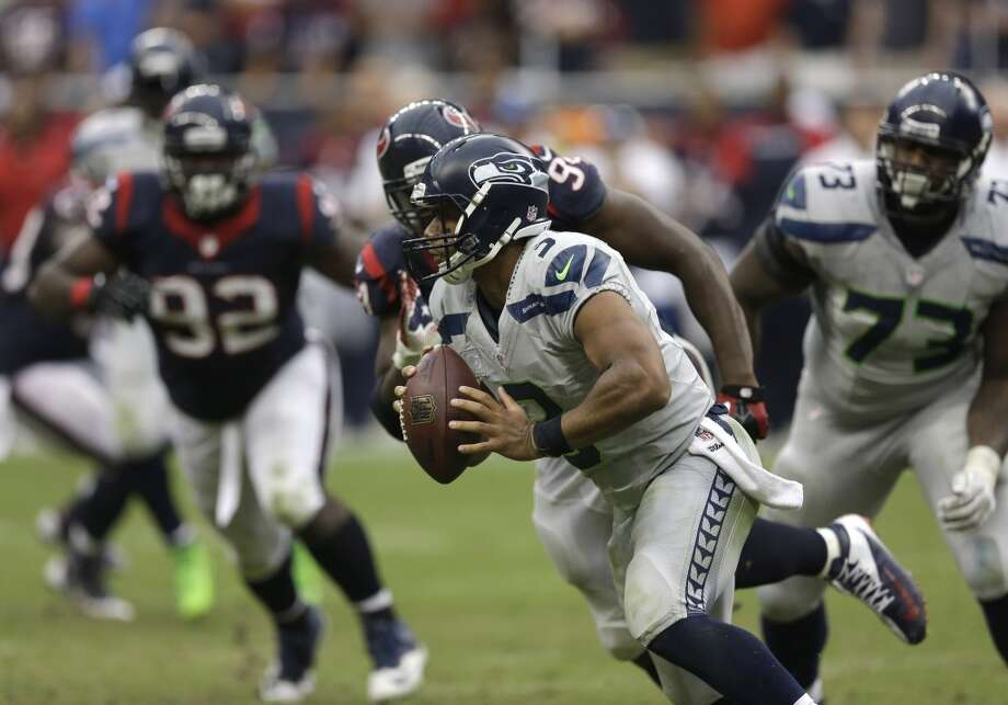 Seattle Seahawks quarterback Russell Wilson (3) scrambles away from Houston Texans defensive end Antonio Smith (94) during overtime of an NFL football game Sunday, Sept. 29, 2013, in Houston. Seattle won 23-20. Photo: David J. Phillip, Associated Press