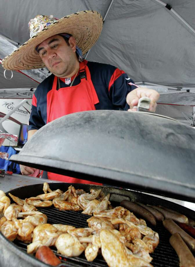 A Houston Texans fans grills before an NFL football game against the Seattle Seahawks, Sunday, Sept. 29, 2013, in Houston. (AP Photo/Patric Schneider) Photo: Patric Schneider, Associated Press / FR170473