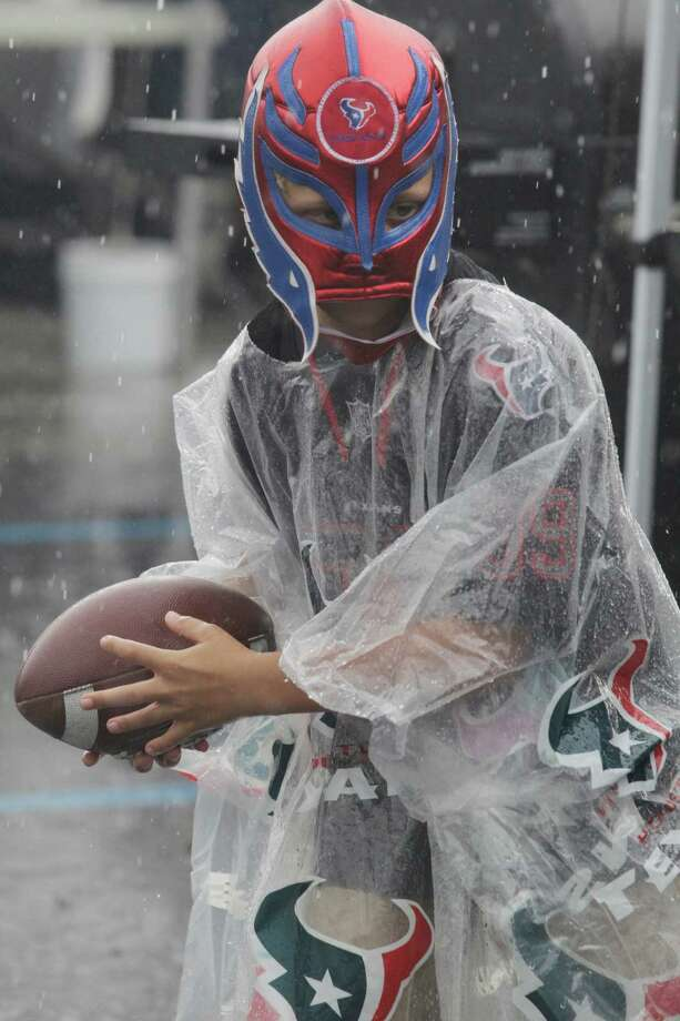 A Houston Texans fan plays in the rain before an NFL football game Seattle Seahawks, Sunday, Sept. 29, 2013, in Houston. (AP Photo/Patric Schneider) Photo: Patric Schneider, Associated Press / FR170473