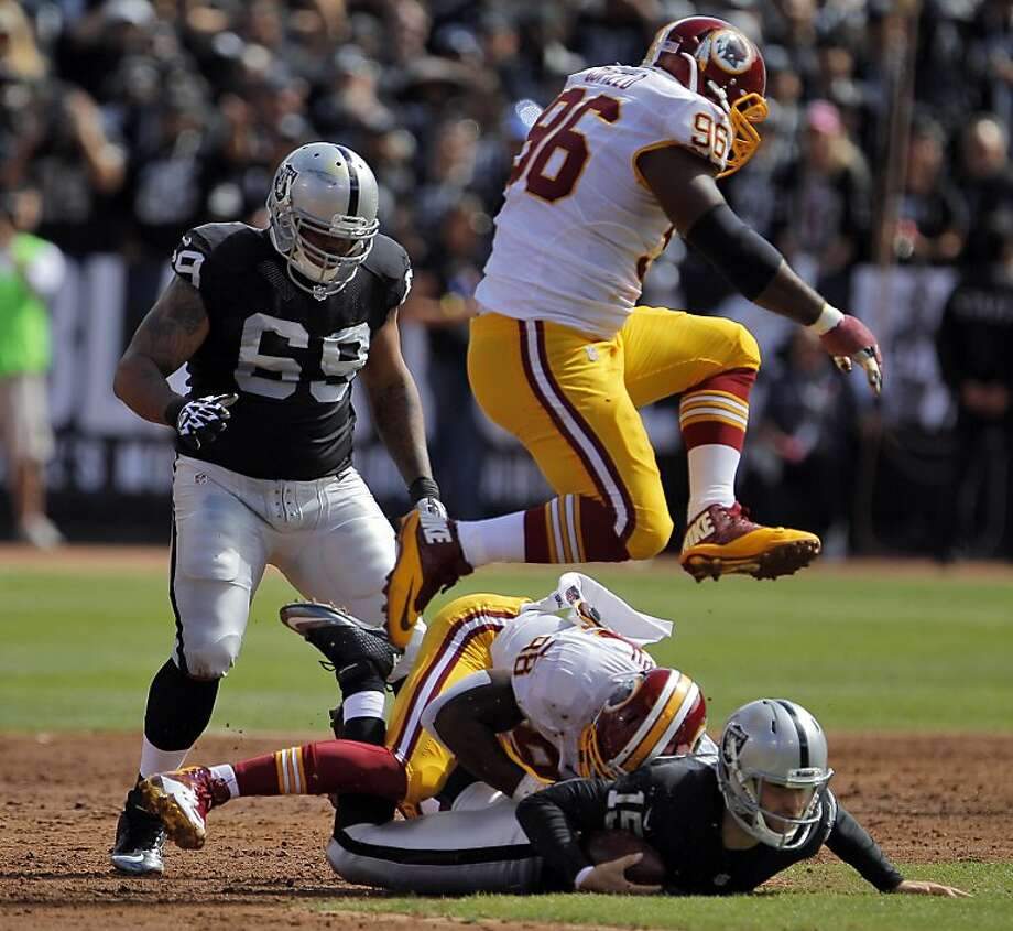 Quarterback Matt Flynn goes down on a sack by Brian Orakpo in the first quarter, the first of seven sacks for Washington. Photo: Carlos Avila Gonzalez, The Chronicle