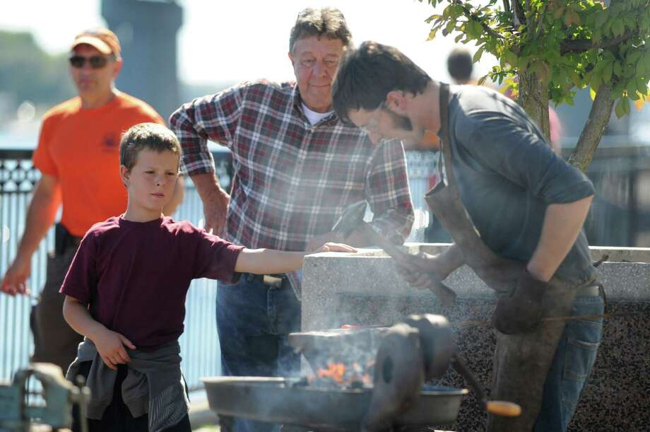 Dorje Bon, 9, of Albany, left, watches Noah Khoury, of The Helderberg Blacksmith, right, forge a nail Sunday afternoon, Sept. 29, 2013, at Jennings Landing in Albany, N.Y., during a demonstration of technologies used during the time of Henry Hudsona€™s voyage up the Hudson River. The event was part of a dockside tour of the The Half Moon, a full-scale operating replica of Hudsona€™s ship, at the Waterfront Pumping Station. (Will Waldron/Times Union) Photo: WW