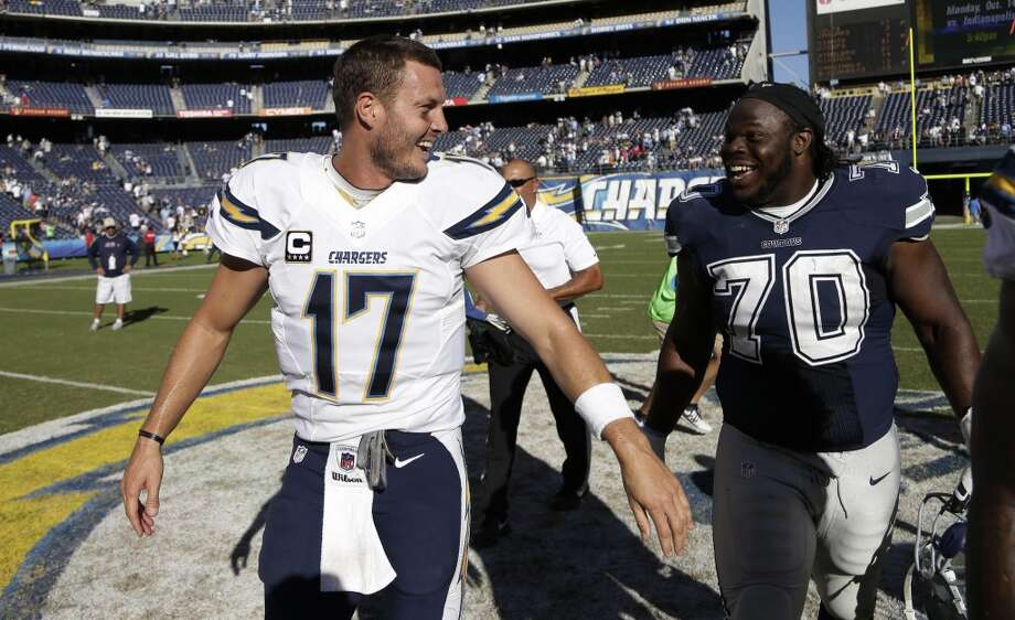 San Diego Chargers quarterback Philip Rivers (17) laughs with Dallas Cowboys defensive tackle Drake Nevis, right, after an NFL football game Sunday, Sept. 29, 2013, in San Diego. The Chargers won, 30-21. (AP Photo/Gregory Bull) Photo: Associated Press