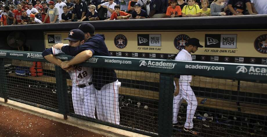 Pitchers Jarred Cosart and Paul Clemens hug in the dugout after the loss. Photo: Karen Warren , Houston Chronicle